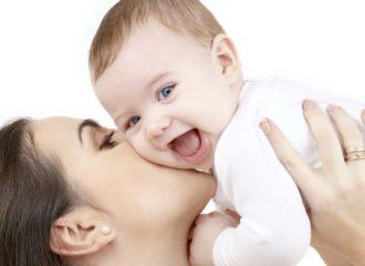 Bébé riant dans les bras de Maman