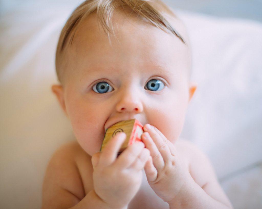 Bébé avec cube à la bouche